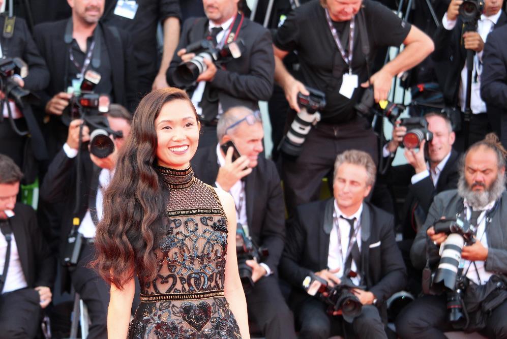 Hong Chau sorride ai fotografi sul red carpet d'apertura di Venezia 74.