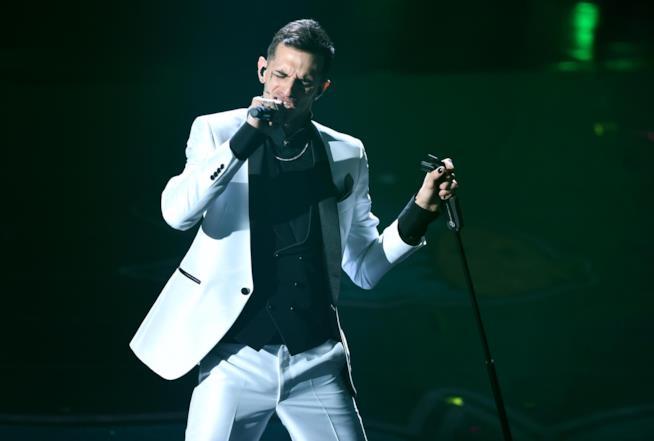 Achille Lauro, vestito di bianco, canta in piedi con in mano il microfono