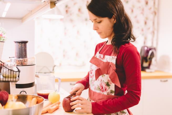 Ragazza che taglia mele per un centrifugato