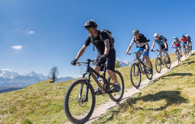 Un gruppo di persone scendono da una montagna in bici