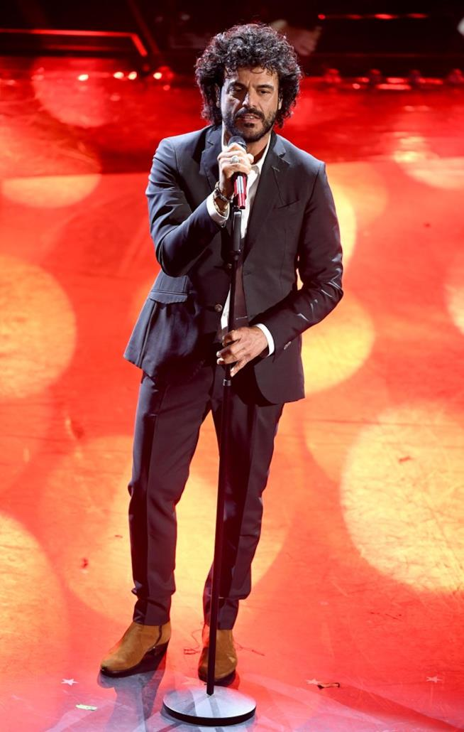 Francesco Renga, in nero, in piedi davanti al microfono su sfondo rosso