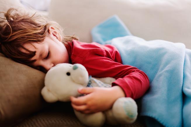 Bambino che dorme con peluche