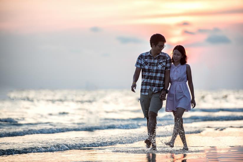 Due ragazzi camminano mano nella mano sulla spiaggia