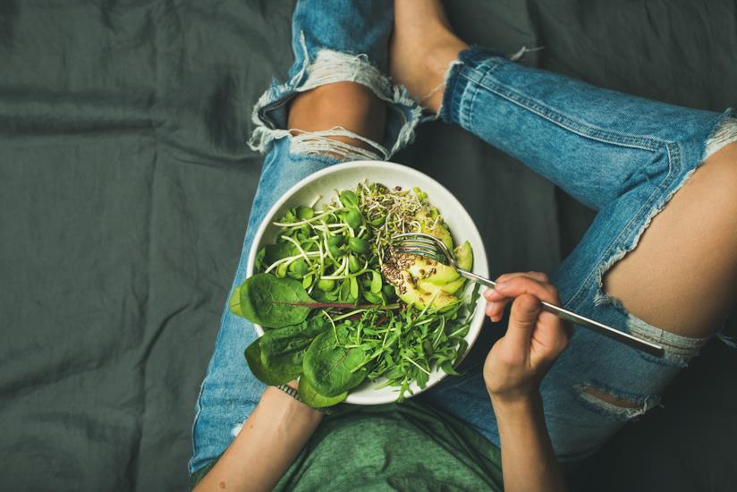 Ragazza con un piatto di verdure crude