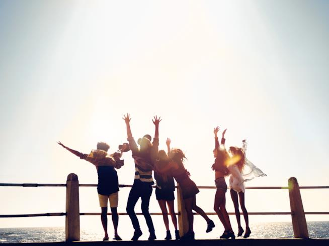 Gruppo di ragazzi che festeggia l'inizio delle vacanze al mare esultando su un pontile