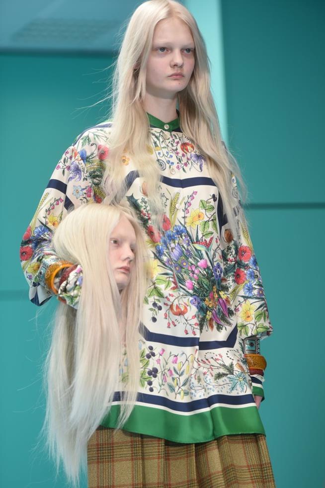 Modella con testa in mano nella sfilata Gucci