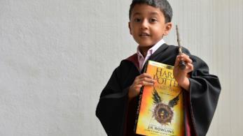 Un bambino, vestito da mago, con in mano la bacchetta e un libro di Harry Potter