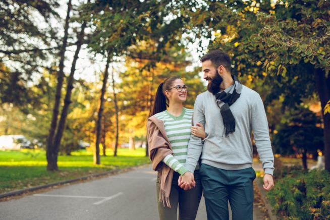 Coppia passeggia in un parco a braccetto