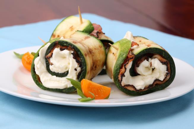 Primo piano su piatto bianco di zucchine alla griglia ripiene di speck e crema di formaggio