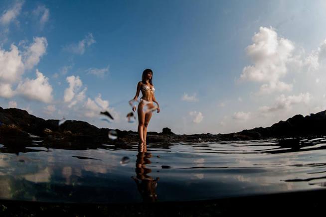 Modella in piedi nel mare con indosso il costume bianco