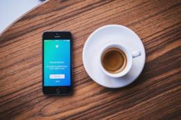 Uno smartphone con Twitter e una tazza di caffè.