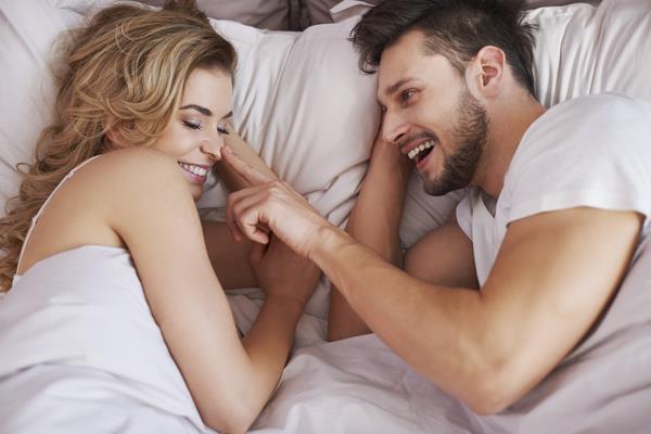 Un ragazzo ed una ragazza sorridono tra le lenzuola
