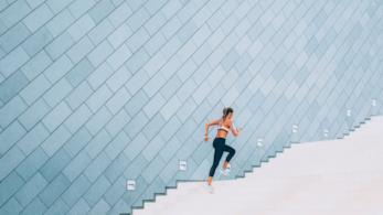 Una ragazza in tenuta sportiva sale una lunga scalinata