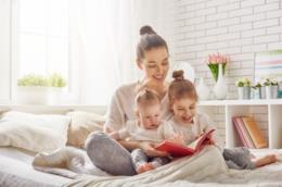 Una madre legge a letto con i figli