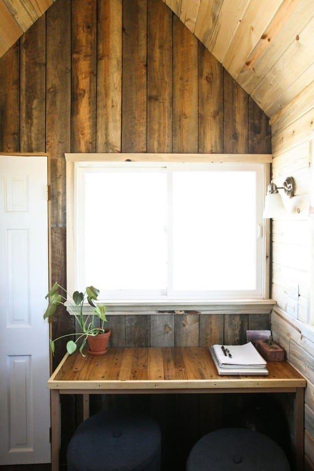 Una piccola scrivania di legno collocata sotto una finestra