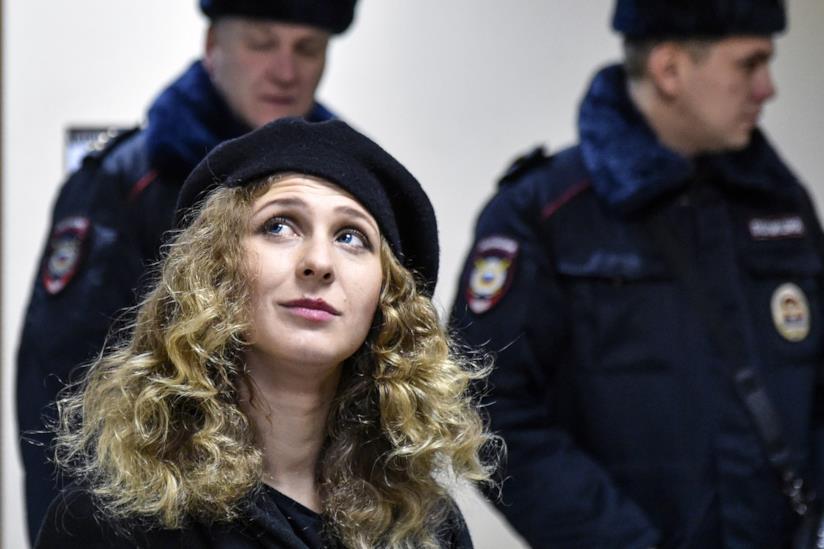 Una ragazza, componente delle Pussy Riot, e due poliziotti