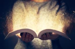 Bambina con un libro aperto tra le mani