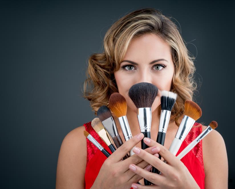 Una donna mostra alcunu pennelli per applicare il fondotinta
