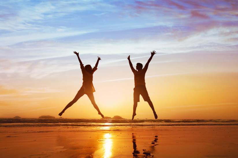 Ragazzo e ragazza saltano felici sulla spiaggia