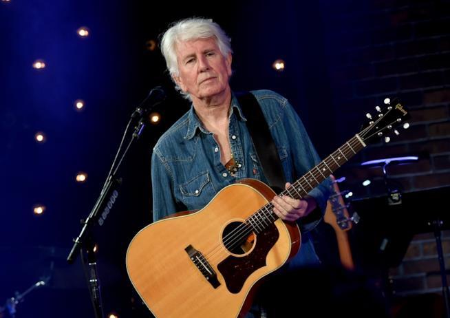 Graham Nash, in piedi, con un giubbetto di jeans, con la chitarra acustica in mano e davanti al microfono