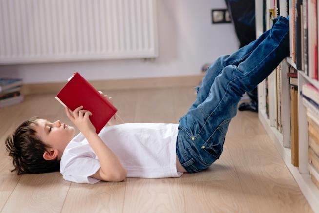 Bambino intento a leggere un libro, sdraiato sul pavimento del soggiorno vicino alla libreria
