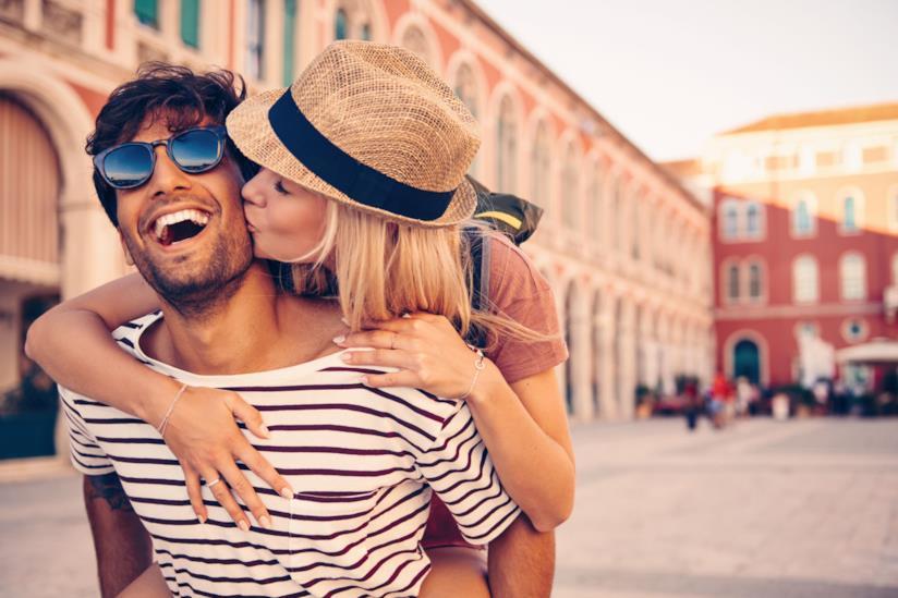 Ragazza sulle spalle del fidanzato lo bacia sulla guancia