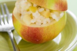 Primo piano di un piatto verde con forchetta, una mela scavata e all'interno riso con le mele