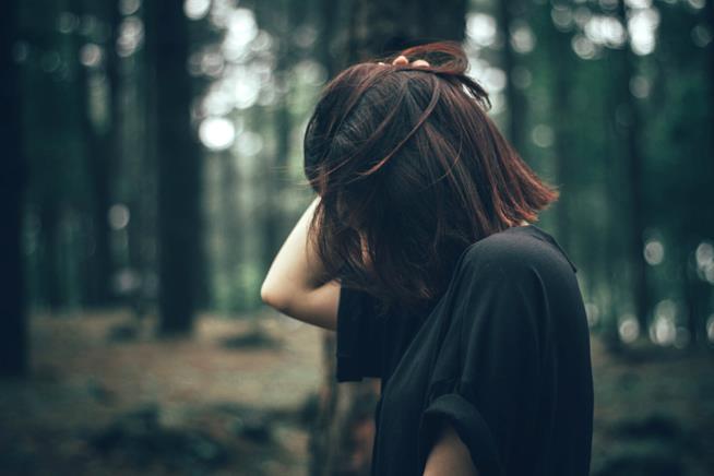 Una ragazza si ravvia i capelli in un bosco