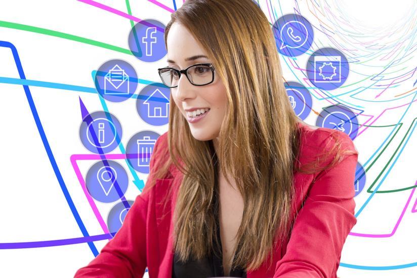 Ragazza seduta al pc con dietro le icone dei social media