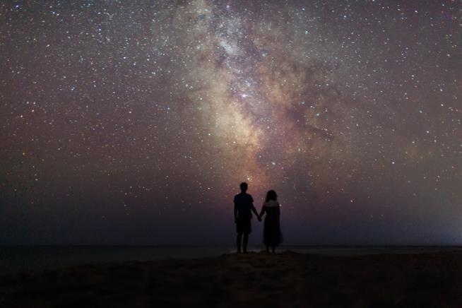 Coppia in penombra si tiene per mano di fronte a un cielo stellato