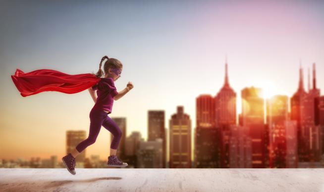 Una bambina corre vestita da supereroe
