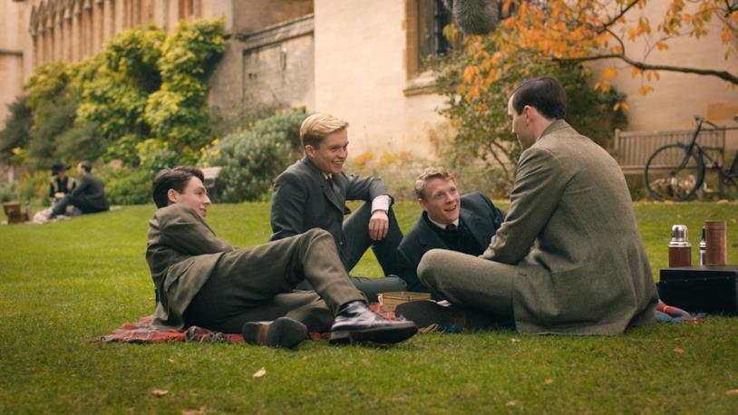 Nicholas Hoult seduto sul prato insieme agli interpreti dei suoi amici, seduti sul prato della scuola