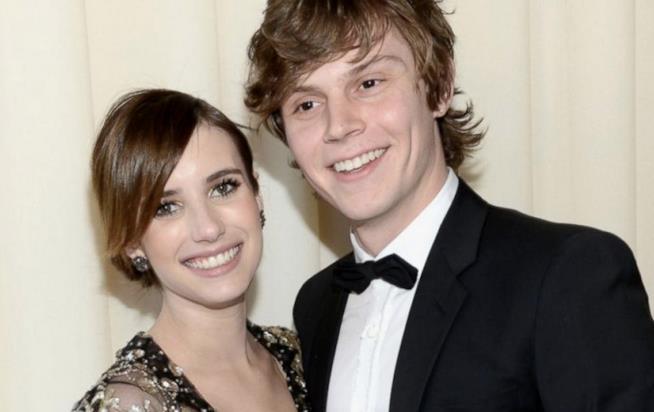 Emma Roberts ed Evan Peters sorridono davanti all'obiettivo di un flash