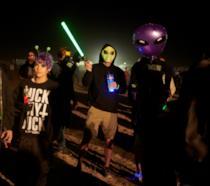 Una foto di spalle di un partecipante al raid dell'Area 51, con un alieno gonfiabile in braccio