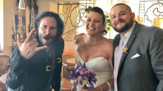 L'attore Keanu Reeves in posa per una foto con una coppia di sposi
