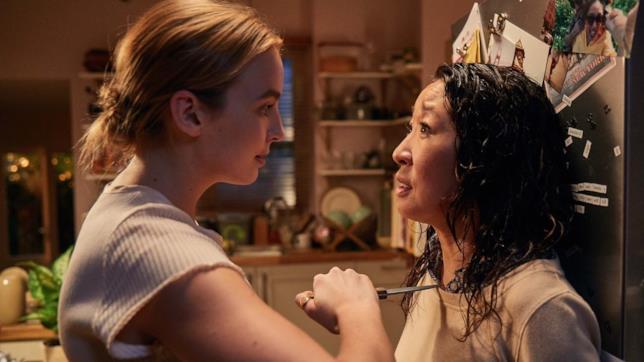 Mezzibusti di Jodie Comer e Sandra Oh all'interno di una cucina. Jodie Comer minaccia Sandra Oh con un coltello