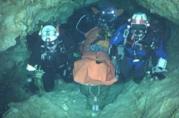 Soccorritori bardati portano fuori dalla grotta un bambino in barella