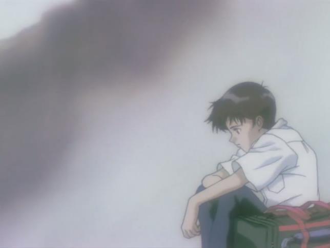 Shinji accovacciato vicino alla sua valigia