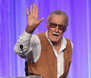 Mezzobusto di Stan Lee che saluta, su sfondo viola