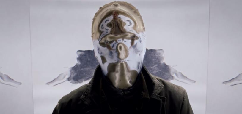 Looking Glass indossa un cappotto nero e una maschera argentata