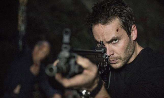 Taylor Kitsch imbraccia un mitra nel ruolo di Ghost, il terrorista di American Assassin