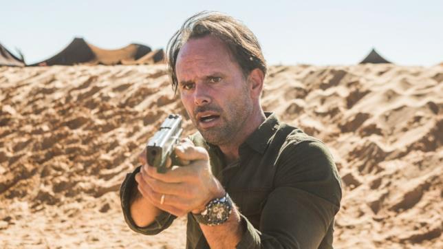 Nathan Miller impugna una pistola in una scena della seconda stagione di Deep State