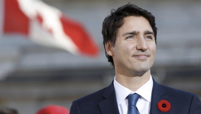 Justin Trudeau con lo sfondo della bandiera canadese