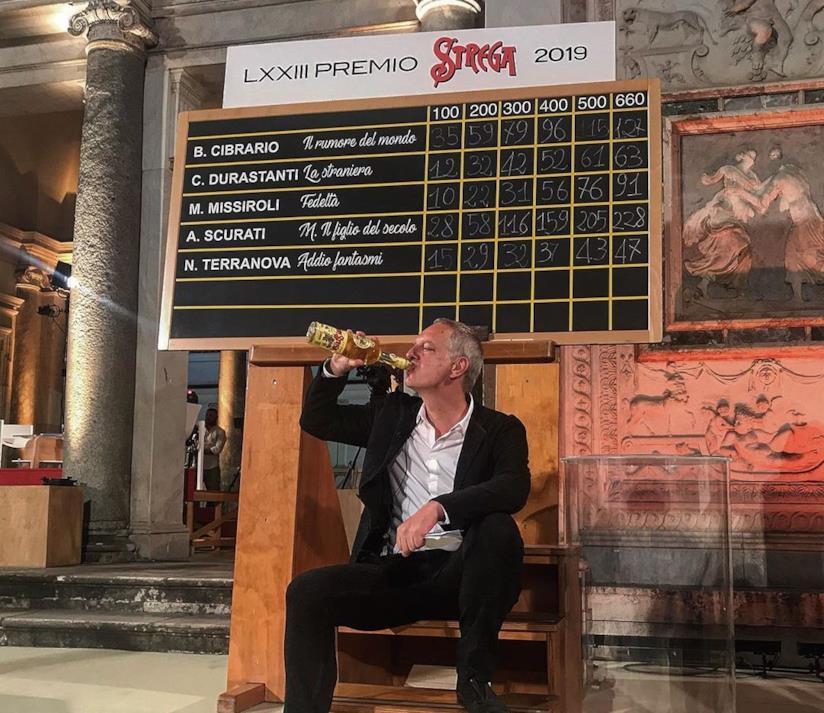 Scurati beva dalla tradizionale bottiglia di Strega