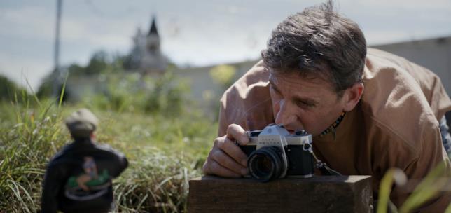 Steve Carell steso sull'erba ad immortalare uno dei suoi soldatini di Marwen