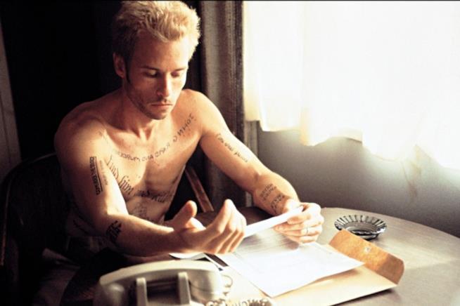 Guy Pearce biondo e con il corpo coperto di tatuaggi in una scena del film
