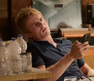 Caleb Haas seduto con telefono in mano