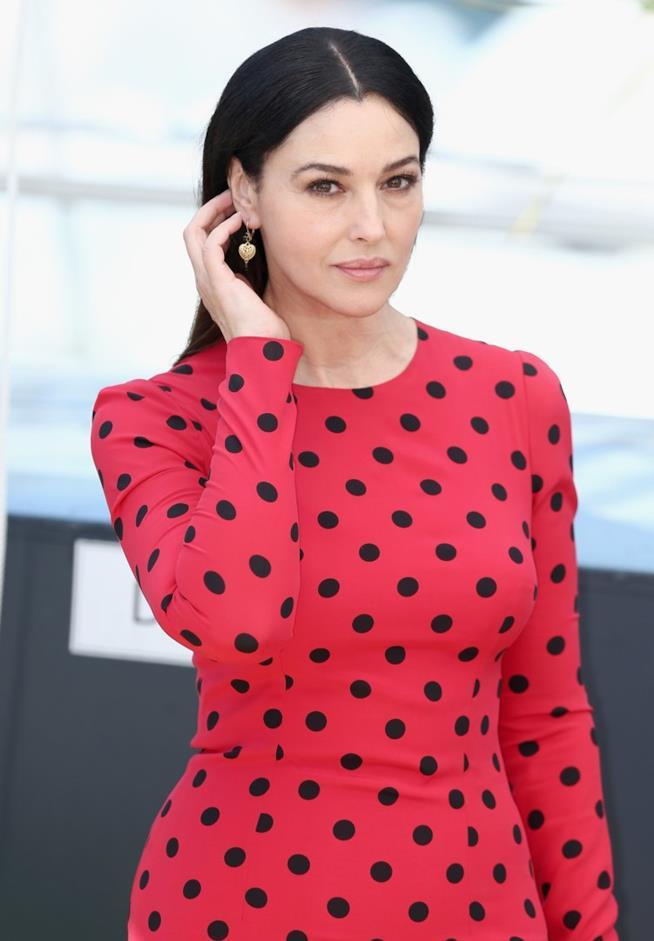 Uno scatto di Monica Bellucci in abito rosso a pois neri, mentre si sistema i capelli dietro l'orecchio