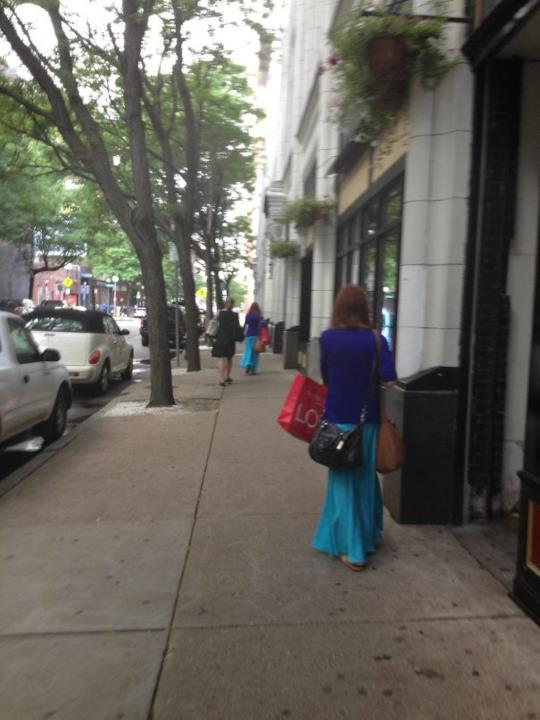 Due donne per strada con lo stesso outfit e shopper