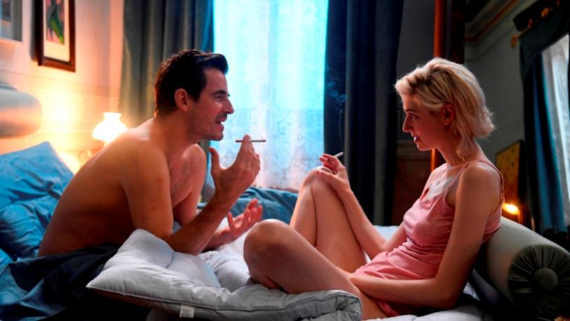 Claes Bang ed Elizabeth Debicki fumano seduti sul letto in una scena del film